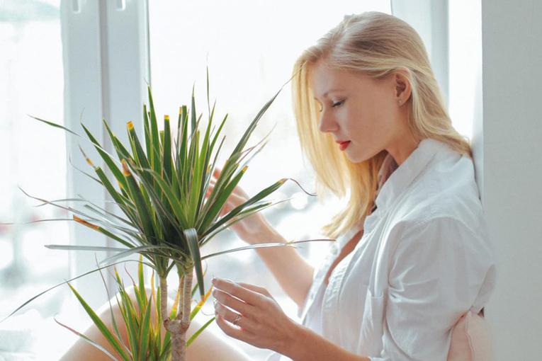 Kadın çiçekle konuşuyor.