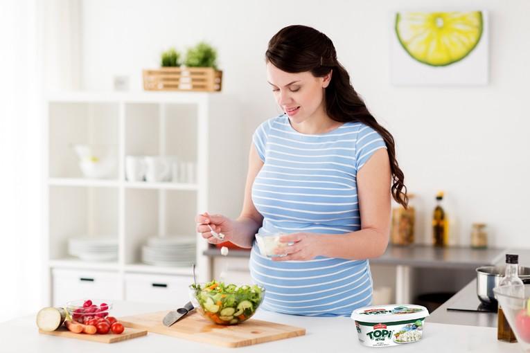 Hamile kadın yemek yapıyor.